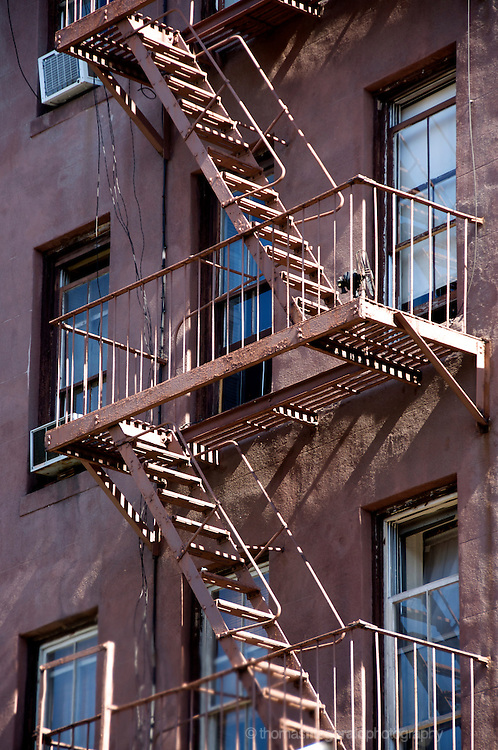 A fire escape painted to match the building behind it with light playing across the fascade.