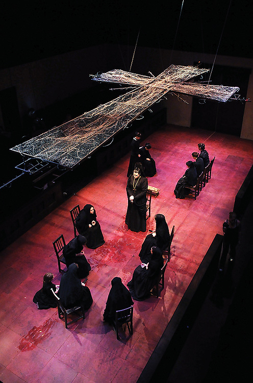 """Beneath a cross that hangs above the set of """"The House of Bernarda Alba"""" Danielle Robinette, who plays Bernarda Alba, rehearses in the Center for the Arts New Studio Theatre Wednesday night. The play premieres Friday, Nov. 30 at 8 p.m..."""