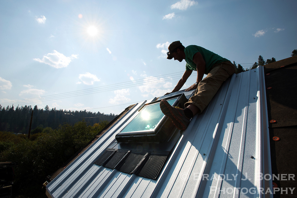 Adam Glos installs the metal roof and skylight on his home in early August.