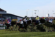 Horses negotiate The Water Jump in the 5:15pm The Randox Health Grand National Steeple Chase (Grade 3) 4m 2f during the Grand National Meeting at Aintree, Liverpool, United Kingdom on 6 April 2019.