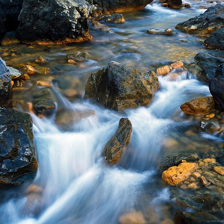 Near the Blahnukur Trail, a small stream flows through the colorful rocks