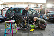 Studenten plakken de band van de fiets, geholpen door hun buurman.<br />