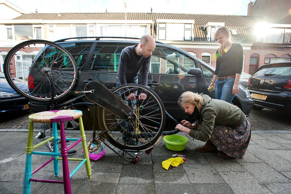 Studenten plakken de band van de fiets, geholpen door hun buurman.<br /> <br /> Two students are repairing a flat tire, helped by their neighbor.