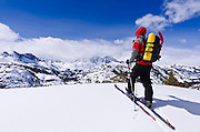Backcountry skier under Banner and Ritter Peaks in the Ansel Adams Wilderness, Sierra Nevada Mountains, California USA