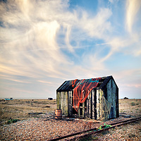 Hut with fishing net on deserted beach at Dungeness, East Sussex, UK