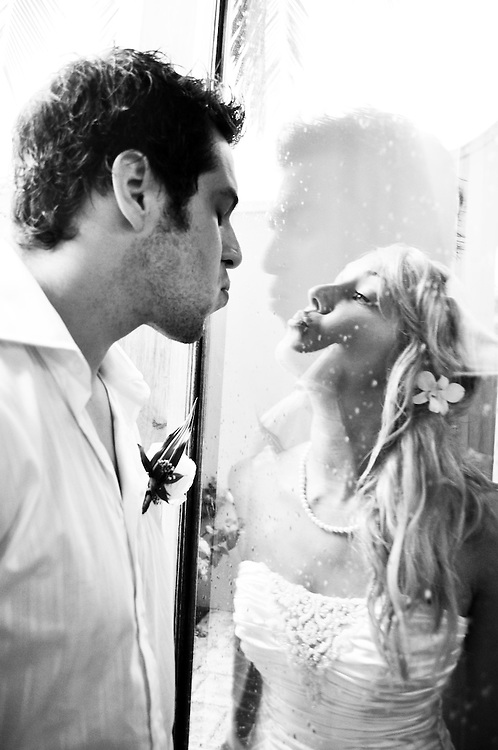 Amy & Sebastien make funny faces at each other through a rain speckled door at Dreams Resort, Tulum, Mexico