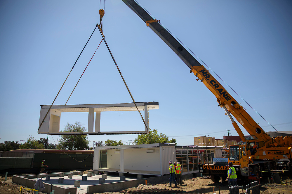 Construction workers and riggers use a crane to lift prefabricated classroom sections made of recycled shipping containers into position at Vaughn Next Century Learning Center on Friday, April 21, 2017 in San Fernando, Calif. A new project will provide upgraded classrooms on an L.A. Unified campus that hosts a charter school, replacing 21 old portable classrooms with new construction classrooms made with recycled shipping containers. © 2017 Patrick T. Fallon