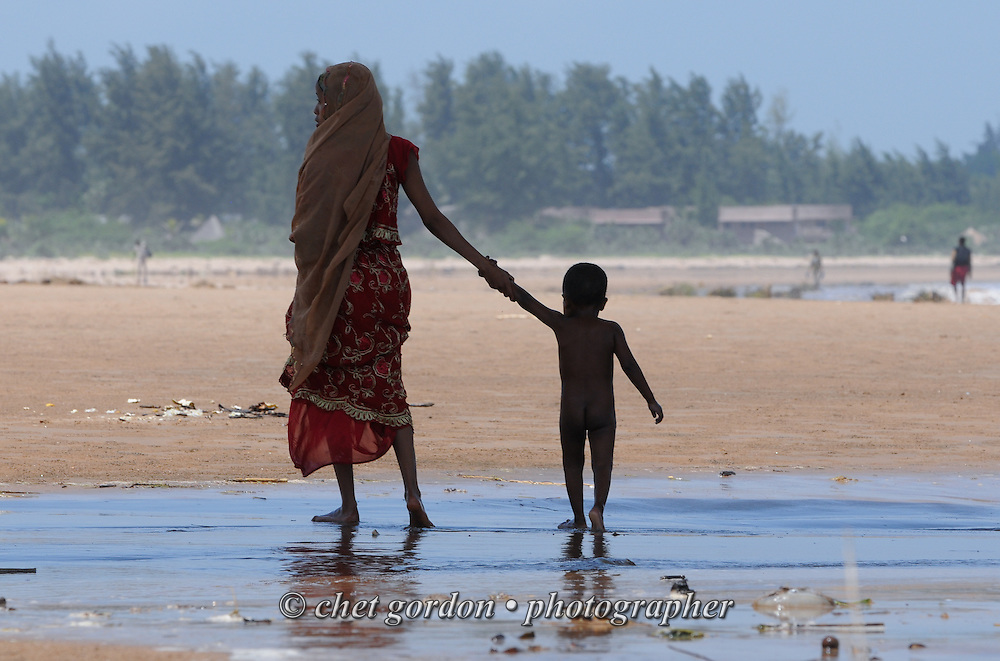 A Young Muslim mother strolls the beach with her son under a concrete pier in Malindi, Kenya on December 9, 2011.