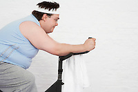 Overweight man on Exercise Bike side view