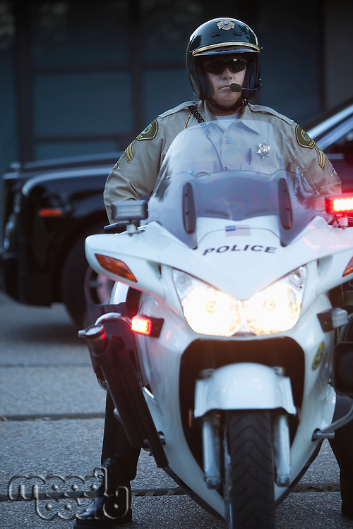 Patrol officer sits on motorcycle with hazrd lights lit