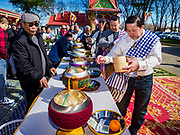 14 APRIL 2019 - DES MOINES, IOWA: Men make an offering at the Tak Bat during Lao New Year, also called Songkran,  observances at Wat Lao Buddhavath in Des Moines. Several thousand Lao people live in Des Moines. Most came to the US after the wars in Southeast Asia. Songkran is celebrated in Theravada Buddhist countries (Sri Lanka, Myanmar, Thailand, Laos, and Cambodia) and in Theravada Buddhist communities around the world.         PHOTO BY JACK KURTZ
