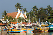 Negombo. Boats berthed at the lagoon mooring on a Sunday. .Anglican church in the background.
