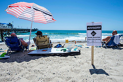 June 14, 2017 - San Clemente, California, USA - Beach goers sit next to a shark advisory sign as they enjoy the summer sun near the San Clemente Pier on Wednesday, June 14, 2017. The Heal the Bay's new beach report card lists the San Clemente Pier area in San Clemente, as one of the ten worst in the state for bacteria pollution.  (Photo by Mark Rightmire, Orange County Register/SCNG) (Credit Image: © Mark Rightmire, Mark Rightmire/The Orange County Register via ZUMA Wire)