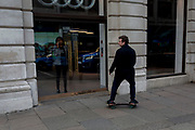 An adult skates past an Audi showroom where an employee makes a phone call in Mayfair, on 21st March 2017, in London, England.