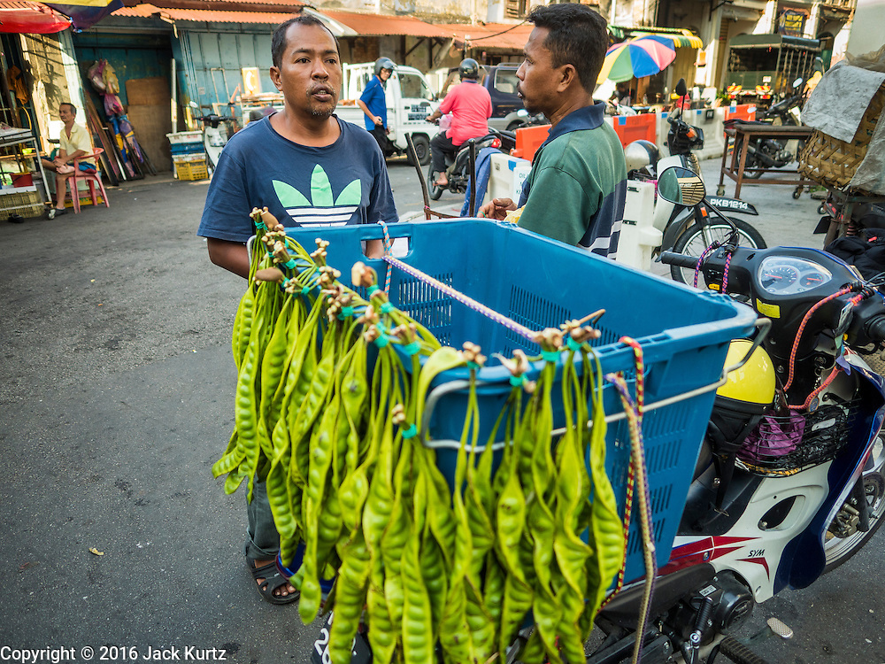 """17 NOVEMBER 2016 - GEORGE TOWN, PENANG, MALAYSIA:  A man sells """"stink beans"""" (called that because they have a sharp odor when cooked) in a market in George Town, Penang, Malaysia. George Town is a UNESCO World Heritage city and wrestles with maintaining its traditional lifestyle and mass tourism.       PHOTO BY JACK KURTZ"""