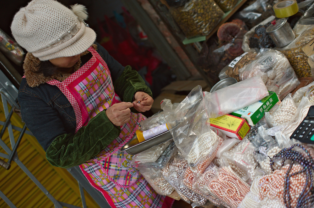 Woman stringing pearls at street market, Guangzhou, China