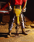 Construction worker using a jackhammer at night.