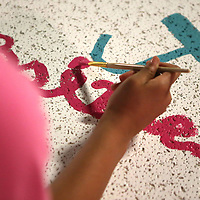 Jordan Akins, 12, of Tupelo, paints her name on her bulletin board art project during SHINE Camp at HealthWorks in Tupelo. SHINE Camp is week long camp put on by the Junior Auxiliary of Tupelo for upcoming middle school girls that promotes positive self-esteem through devotions, drama, art, physical excerise and group discussions.