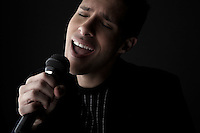 Young man singing into microphone close-up