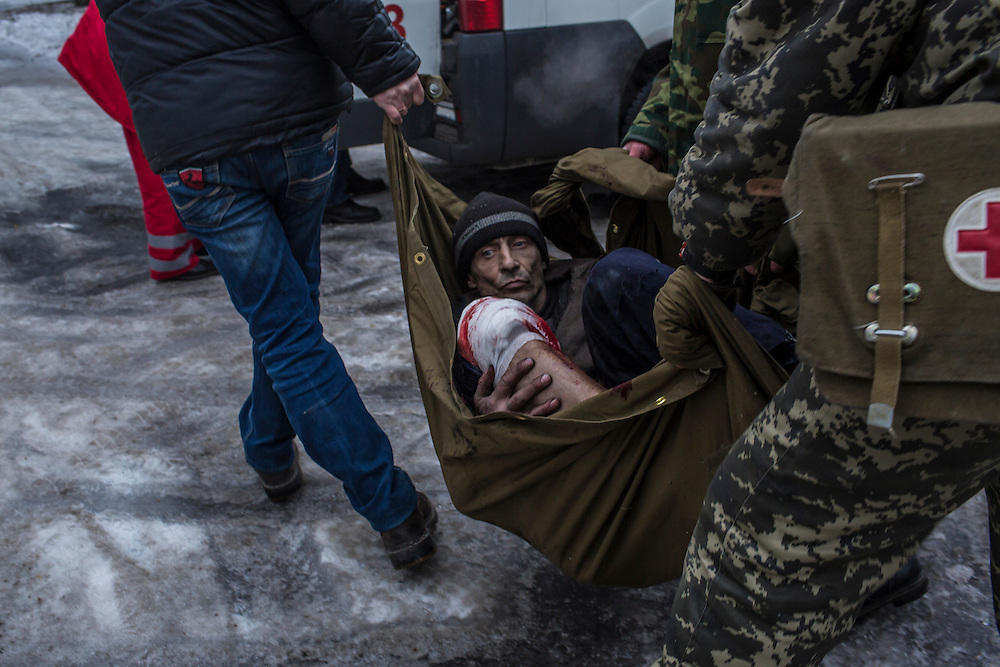 DONETSK, UKRAINE - JANUARY 28, 2015: A man injured by shelling is transferred to an ambulance to be taken to a hospital in the Petrovskyi district of Donetsk, Ukraine. The area, in the city's southwest, is close to heavy front-line fighting in Marinka. CREDIT: Brendan Hoffman for The New York Times