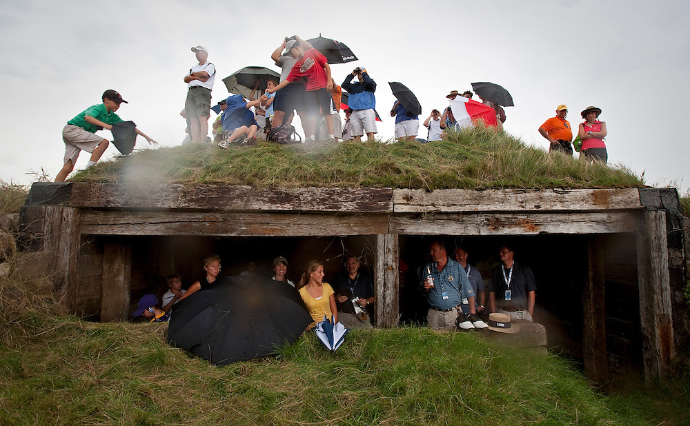 pga14, spt, lynn, 7.-Spectators take cover in a bunker behind the 6th green while others used umbrella's at Whistling Straits during the second round of the PGA Championship Friday August 13, 2010.  The wind shifted and became much stronger along with rain showers late in the day.  Photo by Tom Lynn/TLYNN@JOURNALSENTINEL.COM