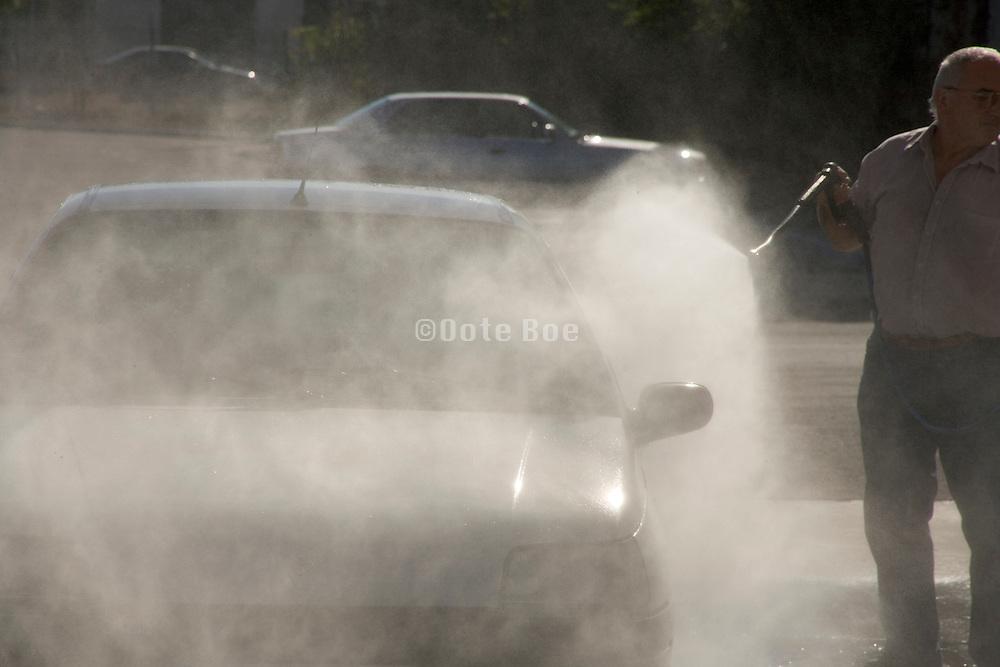 man washing his car at a self service car wash