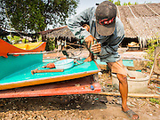 11 APRIL 2014 - PHANTHAI NORASING, SAMUT SAKHON, THAILAND: A man repairs his boat in Phanthai Norasing, Samut Sakhon province. Samut Sakhon is a coastal province southwest of Bangkok. It's known for its fishing and aquaculture industries but manufacturing companies are buying large plots of lands and building factories in the province, supplanting the traditional industries. A large number of Burmese migrants who work in the fishing and manufacturing sectors live in Samut Sakhon.      PHOTO BY JACK KURTZ