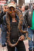 A biker poses with his boa constrictor snake on Main Street during the 74th Annual Daytona Bike Week March 7, 2015 in Daytona Beach, Florida.