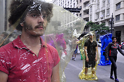 July 26, 2018 - Sao Paulo, Sao Paulo, Brazil - The Intervention of the Minimum Collective called ''EUPRESENTE'' took place on 26 July 2018, in Sao Paulo, Brazil. Bodies present. A color that inhabits a package. A body that inhabits a color. A gift that inhabits a space. A reflection on encapsulated man and the difficulty of contact, man consumption and exacerbated consumption man. (Credit Image: © Cris Faga/NurPhoto via ZUMA Press)