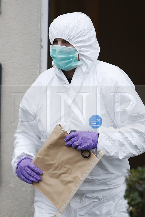 © Licensed to London News Pictures. 05/01/2019. Farnham, UK. Police forensics officers carry evidence bags from a property where a couple were arrested in connection with the murder of a man on a train yesterday. A murder investigation has been launched after the man was attacked while on board the 12. 58pm train service travelling between Guildford and London Waterloo. A man and a woman have been detained by police in Farnham in connection with the murder. Photo credit: Peter Macdiarmid/LNP
