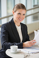 Portrait of confident businesswoman with documents sitting at office cafe