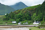 People strolling on beach by cottages and a church at the side of Loch Linnhe at Kingairloch in the Western Highlands of Scotland