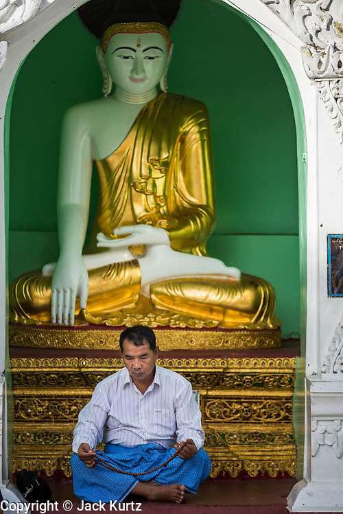 07 JUNE 2014 - YANGON, YANGON REGION, MYANMAR: A man prays in front of a statue of the Buddha at Shwedagon Pagoda in Yangon (Rangoon), Myanmar (Burma). Shwedagon Pagoda is officially called Shwedagon Zedi Daw and is also known as the Great Dagon Pagoda and the Golden Pagoda. It's a 99 metres (325 ft) gilded pagoda and stupa located in Yangon. It is the most sacred Buddhist pagoda in Myanmar with relics of the past four Buddhas enshrined within: the staff of Kakusandha, the water filter of Koṇāgamana, a piece of the robe of Kassapa and eight strands of hair from Gautama, the historical Buddha.   PHOTO BY JACK KURTZ