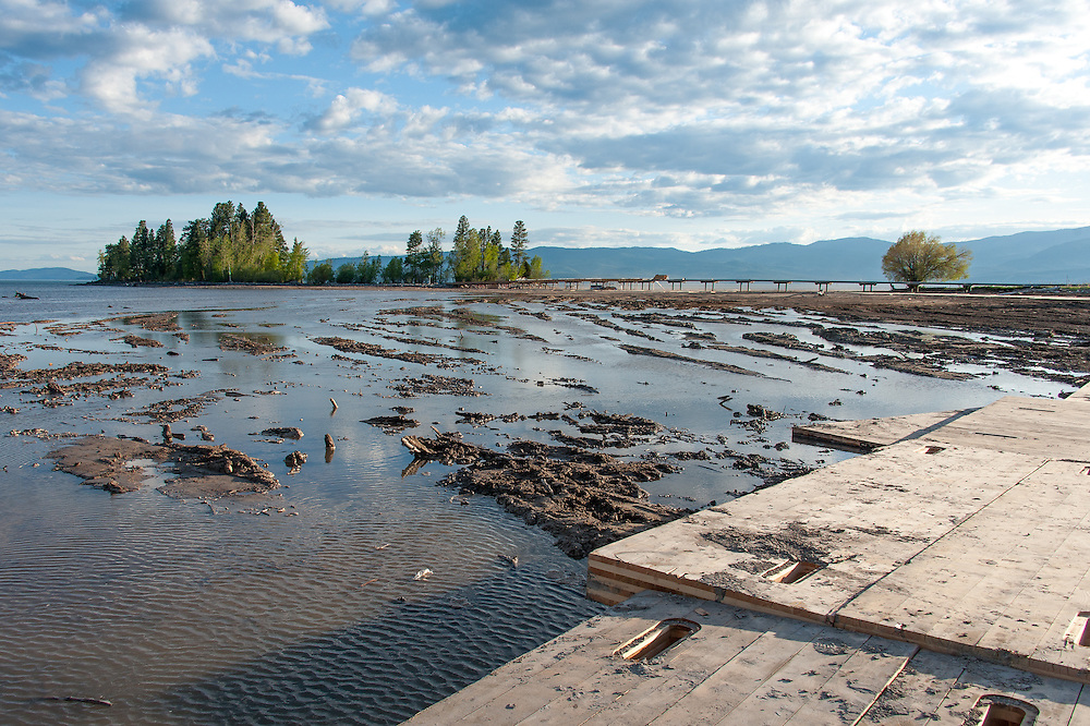 Illegally placed structural panels used to keep cement trucks from getting stuck in the lakebed. Note the lake waters touching the panels. Destruction of the lakebed and the resulting loss of scenic value to the area caused by construction of a private bridge to Dockstader Island on the north shore of Flathead Lake in Bigfork, Montana, in violation of the state's Lakeshore Protection Act, as photographed on May 20, 2015.