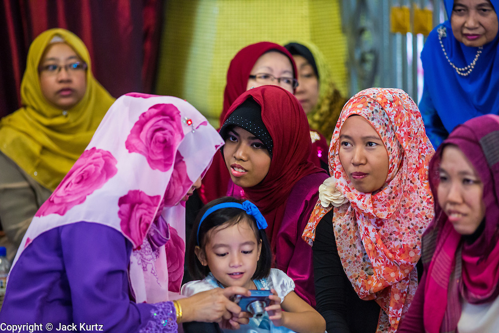 22 DECEMBER 2012 - SINGAPORE, SINGAPORE:  Women at a wedding at the Sultan Mosque in Singapore. The Sultan Mosque is the focal point of the historic Kampong Glam area of Singapore. Also known as Masjid Sultan, it was named for Sultan Hussein Shah. The mosque was originally built in the 1820s. The original structure was demolished in 1924 to make way for the current building, which was completed in 1928. The mosque holds great significance for the Muslim community, and is considered the national mosque of Singapore. It was designated a national monument in 1975.           PHOTO BY JACK KURTZ
