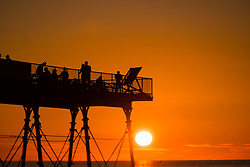&copy; Licenced to London News Pictures. <br /> Aberystwyth Wales UK, Wednesday 25 July 2018. UK Weather: People  are silhouetted by the glorious setting sun over Aberystwyth pier at the end of a day of hot summer sunshine.  The UK wide heatwave continues, with little respite from the very dry weather  despite some rain in the forecast for the weekend. hoto credit: Keith Morris / LNP