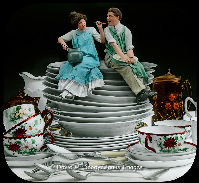 Young married couple sitting on dishes as the wife feeds the husband while they share the work of doing dishes, circa 1910.  Vintage Image: Hand tinted special effects photo