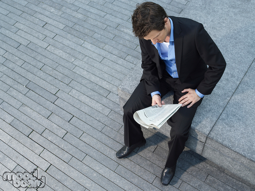Young businessman sitting on wall on pavement reading newspaper elevated view