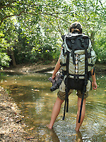 Young woman carrying backpack standing in water back view
