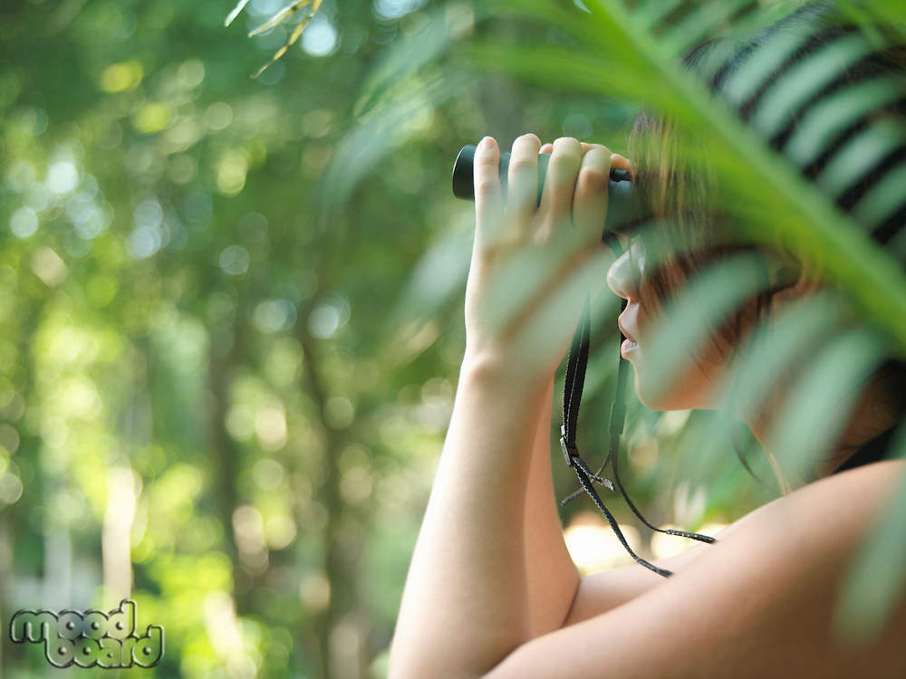 Young woman using binoculars in tropical forest side view