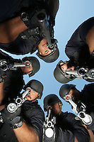 Group portrait of Swat officers standing in circle aiming guns