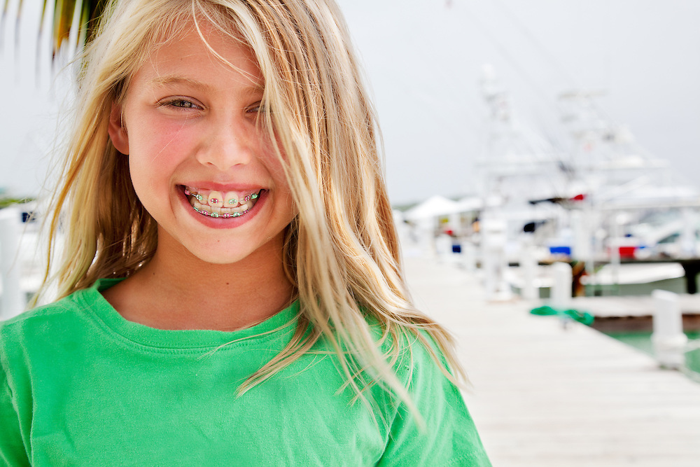 10 yr old blond caucasian girl smiling wearing green shirt on boat dock