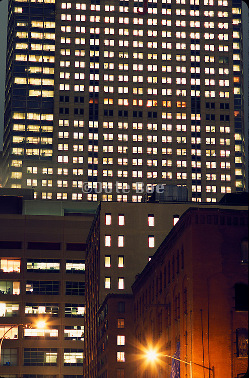nocturnal office high rise behind old warehouse building