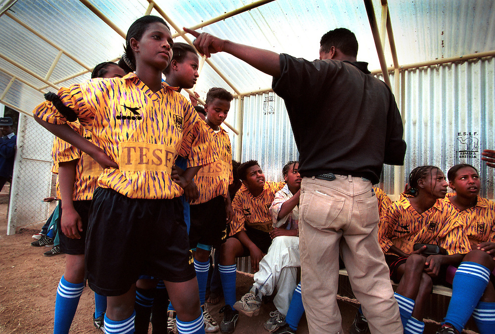 An Eritrean girls football team gets instructions from their disabled coach in half time, during a friendly match at the Denden School in Asmara, Eritrea