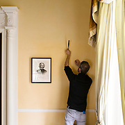"""October 13, 2015 - New York, NY : A curated reinstallation of art and antiques is currently underway in the Mayor's House, Gracie Mansion, as it is being prepped for reopening. Here, Jonathan Elliott, the consulting registrar for the Gracie Mansion Conservancy, hangs works including """"Frederick Douglass (1818 - 1895), ca. 1873,"""" a piece from the Museum of the City of New York, at left, on Tuesday. CREDIT: Karsten Moran for The New York TImes"""