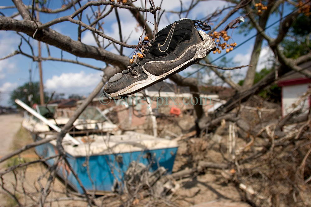 01 October, 05.  New Orleans, Louisiana. Lower 9th ward. Hurricane Katrina aftermath. <br /> The remnants of the lives of ordinary folks, now covered in mud as the flood waters recede. A Nike sneaker hangs in a tree, a washed up boat in the background.<br /> Photo; &copy;Charlie Varley/varleypix.com