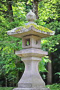 A close-up of a stone lantern at Iwaki shrine on the side of Mt. Iwaki which is a volcano and a very sacred mountain.