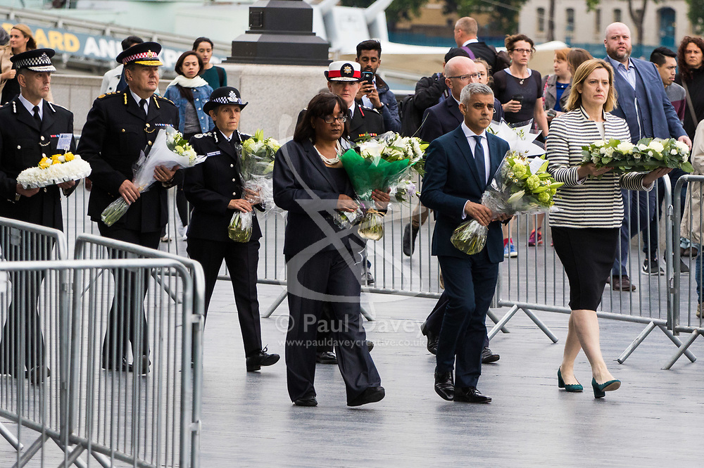 City Hall, London, June 5th 2017.  Mayor of London Sadiq Khan flanked by Labour's Shadow Home Secretary Dianne Abbott (L) and Home Secretary Amber Rudd and followed by emergency services chiefs including Met Commissioner Cressida Dick arrive with flowers at a vigil held in remembrance of those killed during the June 3rd terror attack at London Bridge and Borough Market.