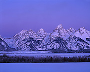 The Teton Range in pre-sunrise Alpenglow is a mountain range of the Rocky Mountains in North America. A north-south range, it is on the Wyoming side of the state's border with Idaho, just south of Yellowstone National Park. Most of the range is in Grand Teton National Park.<br /> <br /> Early French Voyageurs used the name &quot;les Trois T&eacute;tons&quot; (the three breasts).[1] It is likely that the Shoshone people once called the whole range Teewinot, meaning &quot;many pinnacles&quot;.[2]<br /> <br /> The principal summits of the central massif, sometimes referred to as the Cathedral Group, are Grand Teton (13,770 feet (4,200 m)), Mount Owen (12,928 feet (3,940 m)), Teewinot (12,325 feet (3,757 m)), Middle Teton (12,804 feet (3,903 m)) and South Teton (12,514 feet (3,814 m)). Other peaks in the range include Mount Moran (12,605 feet (3,842 m)), Mount Wister (11,490 feet (3,500 m)), Buck Mountain (11,938 feet (3,639 m)) and Static Peak (11,303 feet (3,445 m)).
