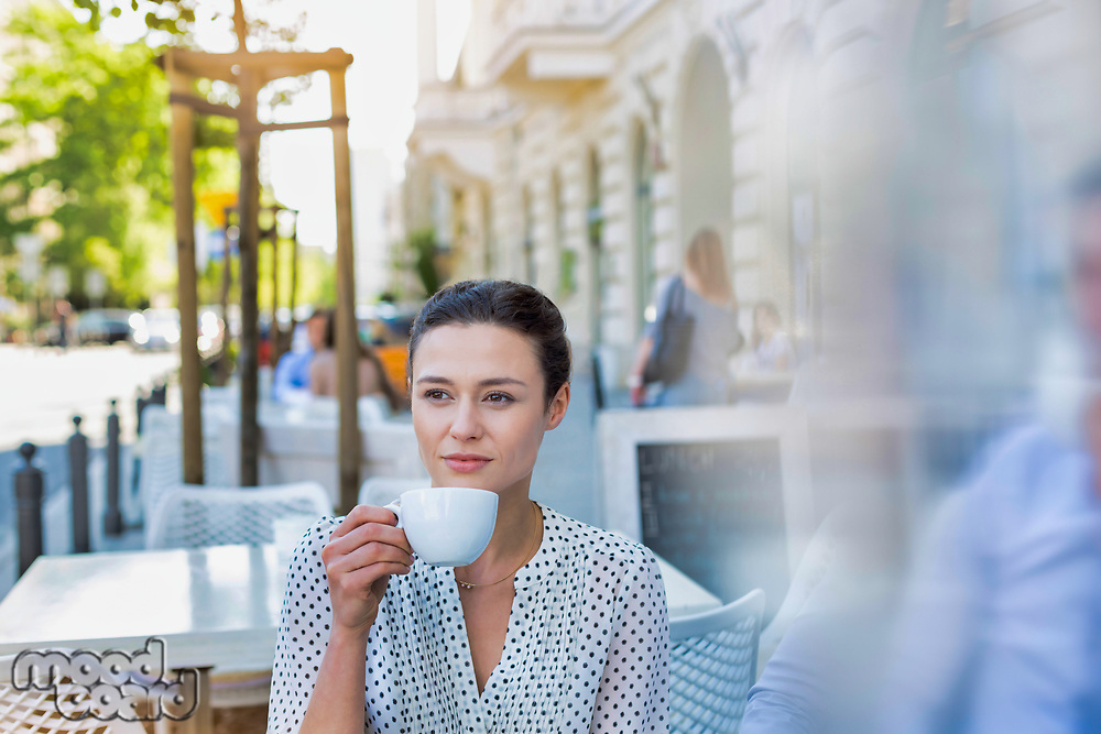 Portrait of young thoughtful and attractive businesswoman sitting while drinking coffee in cafe